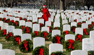 Pati Redmond of Frederick, Md., places wreaths last weekend on graves at Arlington National Cemetery, where new leadership has improved operations, two government reports say. (Associated Press)