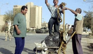 An Iraqi man stands on the head of a statue of Saddam Hussein as U.S. Marines occupy the center of Baghdad on April 10, 2003. But pockets of resistence remained in the northern part of the city and sniper fire could be heard everywhere. The war was far from over. (J.M. Eddins/The Washington Times)