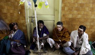 Indian patients receive intravenous saline solution during treatment in a hospital in Diamond Harbour, India, near Kolkata, on Thursday, Dec. 15, 2011, after drinking tainted liquor. (AP Photo/Bikas Das)