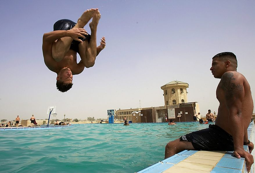 """In this Tuesday, June 7, 2005 file photo, U.S. Army Pfc. Stephen Thomas of Gainsville, Florida jumps into the swimming pool at Camp Victory, in Baghdad, Iraq.  On Friday, Dec. 2, 2011, the base that at its height was home to 46,000 people was handed over to the Iraqi government as part of American efforts to move all U.S. troops out of the country by the end of the year. """"The base is no longer under U.S. control and is under the full authority of the government of Iraq,"""" said U.S. military spokesman Col. Barry Johnson. (AP Photo/Jacob Silberberg, File)"""