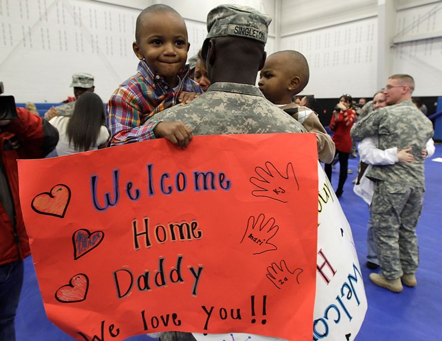 U.S. Army Pfc. Keither Singleton holds his sons Keither Jr., 3, left, and Shamari, 2, right, after he returned home to Joint Base Lewis McChord in Washington state along with other soldiers who had been serving in Iraq , Tuesday, Dec. 6, 2011. (AP Photo/Ted S. Warren)
