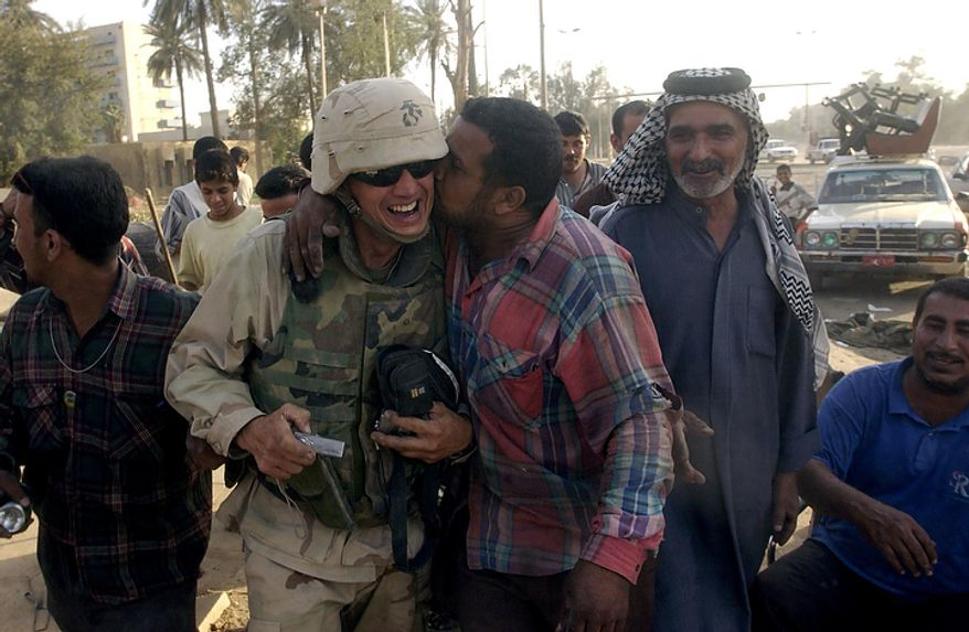 Iraqi citizens greet US Marine Col. J. J. Pomfret of CSSG 11 ( Combat Service Support Group 11 ) near one of Saddam Hussein's palaces on the east bank of the Tigris River in Baghdad, Iraq, Saturday, April 12, 2003. ( J.M. Eddins Jr. / The Washington Times )