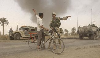 US Marine MP Lance Cpl. Joel Swenson attached to 1st Marines 4th Marine Division directs Baghdad citizens away from convoy routes near the Diyala River in Baghdad, Iraq Wednesday, April 9, 2003. ( J.M. Eddins Jr. / The Washington Times )