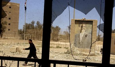 An Iraqi man returns to the headquarters of Saddam Husseins Secret Police to gather more loot in Baghdad, Iraq Friday, April 11, 2003. ( J.M. Eddins Jr. / The Washington Times )