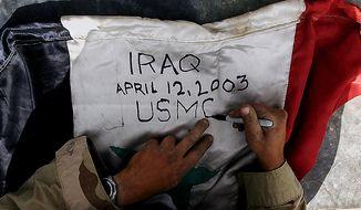 A US Marine signs an Iraqi flag on his way to Tikrit in Northern Iraq Monday, April 14, 2003. ( J.M. Eddins Jr. / The Washington Times )