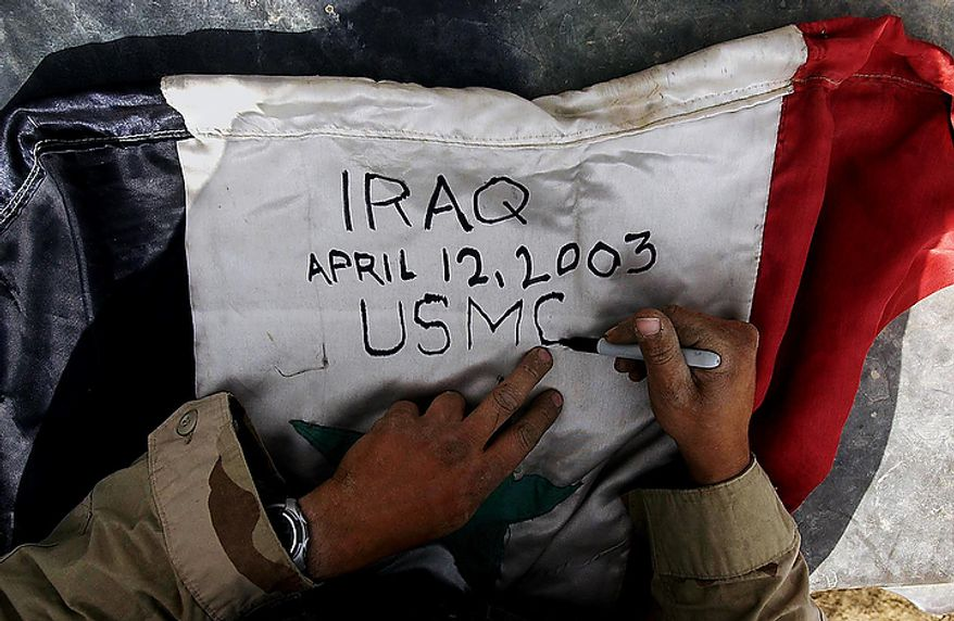 A US Marine signs an Iraqi flag on his way to Tikrit in Northern Iraq Monday, April 14, 2003. ( J.M. Eddins Jr. / The Washington Times )