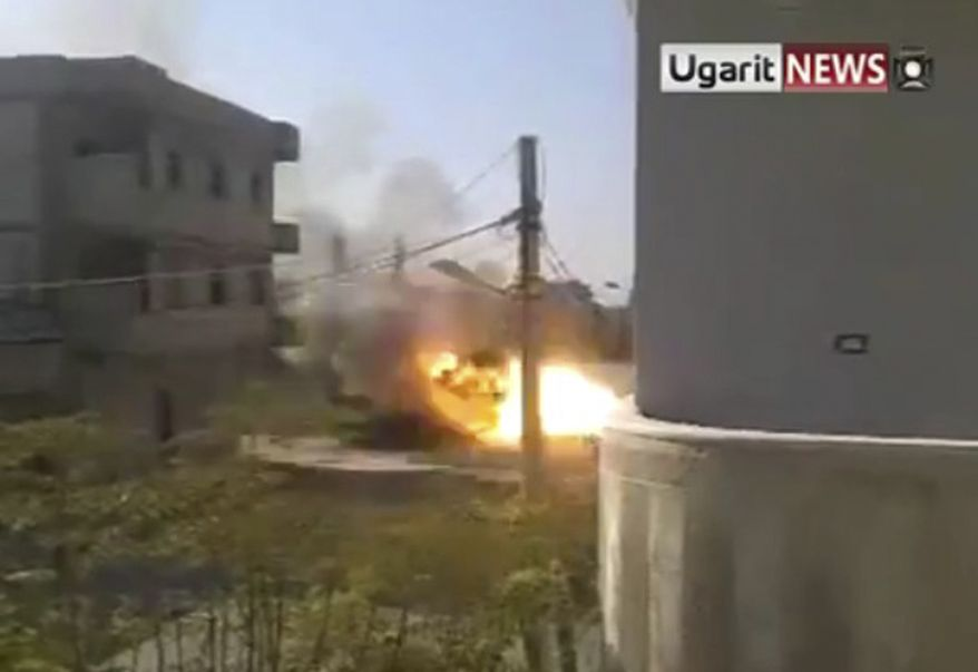 In this image from TV made available by a group called Ugarit News on Thursday, Dec. 15, 2011, amateur footage shows what appears to be a Syrian tank on fire in Homs, Syria, on Wednesday as gunfire rings out and the tank then apparently explodes. (AP Photo)