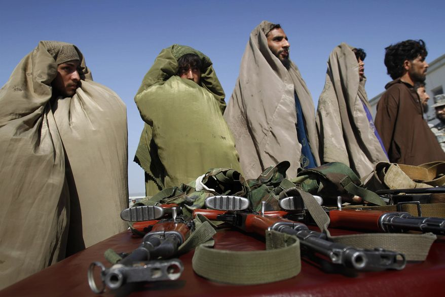 **FILE**  Taliban militants, who were arrested by Afghan Border Police, stand over their guns July 4, 2011, while they are presented to the media at the Afghan Border Police headquarters in Jalalabad, Nangarhar province, east of Kabul, Afghanistan. All of them were dressed as women and at least one was strapped with an explosive vest. (Associated Press)