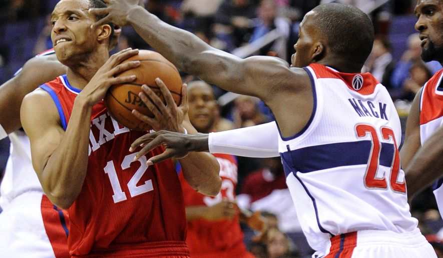 Philadelphia 76ers guard Evan Turner, who had 16 points and seven rebounds, tries to get past Washington Wizards guard Shelvin Mack during the first half, Friday, Dec. 16, 2011, in Washington. (AP Photo/Nick Wass)