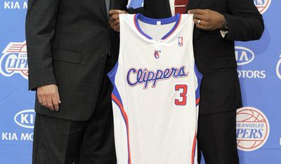 Newly acquired Los Angeles Clippers point guard Chris Paul (right) holds up his jersey Dec. 15, 2011, as he stands with Clippers head coach Vinny Del Negro during a news conference in Los Angeles. (Associated Press)