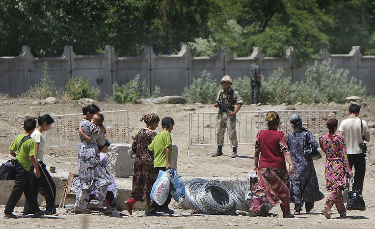 **FILE** Ethnic Uzbeks walk on Uzbekistan territory on June 18, 2010, after crossing the Uzbek-Kyrgyz border near the southern city of Osh as Uzbek border guards look on. (Associated Press)