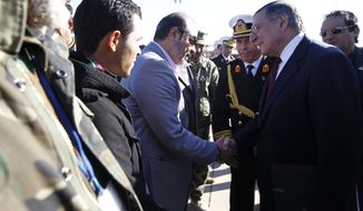U.S. Secretary of Defense Leon E. Panetta greets members of the Libyan delegation on the tarmac during his arrival in Tripoli, Libya, on Saturday, Dec. 17, 2011. (AP Photo/Pablo Martinez Monsivais, Pool)