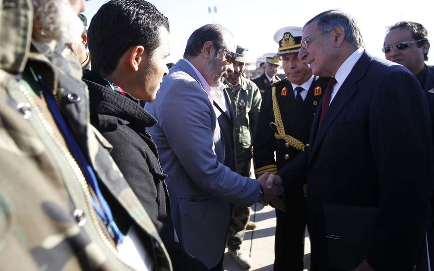 U.S. Secretary of Defense Leon E. Panetta greets members of the Libyan delegation on the tarmac during his arrival in Tripoli, Libya, on Saturday, Dec. 17, 2011. (AP Photo/Pablo Martinez Monsivais, Pool)