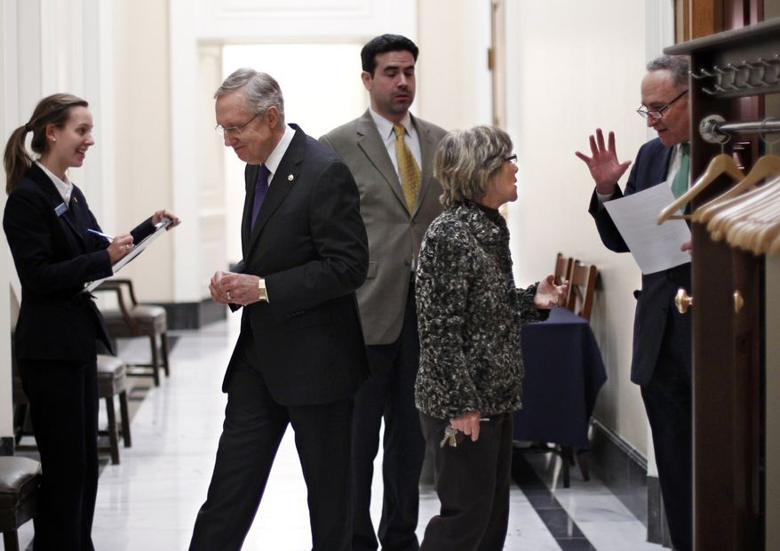 Senate Majority Leader Harry Reid of Nevada , second left, leaves closed-door negotiations on the payroll tax cut extension and other measures as Sen. Chuck Schumer, D-N.Y., far right, speaks with Sen. Barbara Boxer, D-Calif., Friday night, Dec. 16, 2011, at the Capitol in Washington. (AP Photo/J. Scott Applewhite)