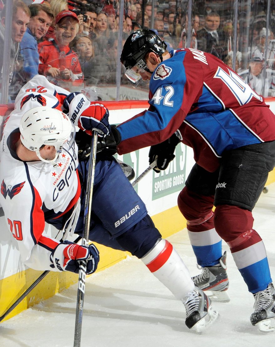 Colorado Avalanche center Brad Malone (42) knocks Washington Capitals left wing Troy Brouwer (20) off his skates during the first period of an NHL hockey game Saturday, Dec. 17, 2011, in Denver. (AP Photo/Jack Dempsey)