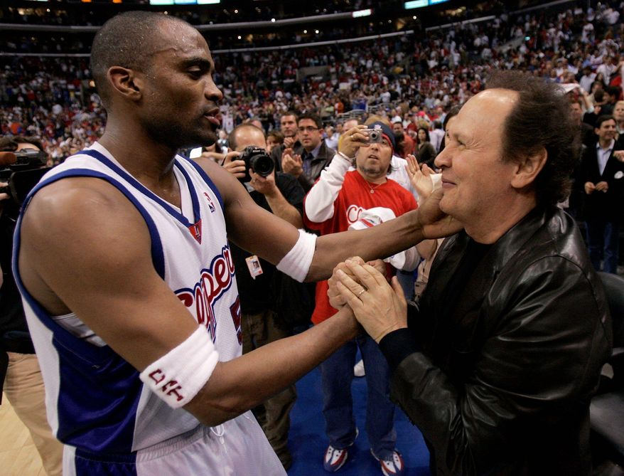 Actor Billy Crystal shakes the hand of a Los Angeles Clipper player after a game. The Clippers play in the same arena as the Los Angeles Lakers. Mr. Crystal is a courtside regular at Clippers' games as is actress-director Penny Marshall. (Associated Press)