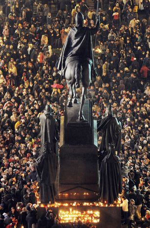 People surround St. Wenceslas statue at Wenceslas Square in Prague on Sunday to pay tribute to Vaclav Havel. The former Czech president died early Sunday morning at his country home in Hradecek, northeast of Prague. He was 75. (Associated Press)