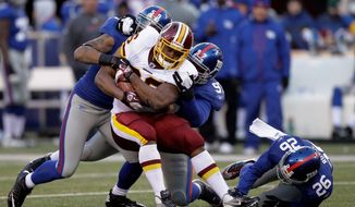 Redskins fullback Darrel Young, stopped here by New York Giants linebacker Michael Boley (59) and defensive tackle Linval Joseph, scored his first touchdown of the season in Washington's win. (Associated Press)