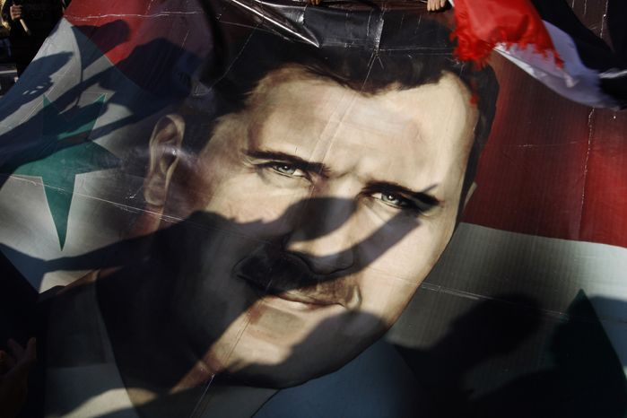 Shadows of Syrians are reflected on a giant poster of Syrian President Bashar Assad during a rally in support of the leader in Damascus, Syria, on Friday, Dec. 16, 2011. (AP Photo/Muzaffar Salman)