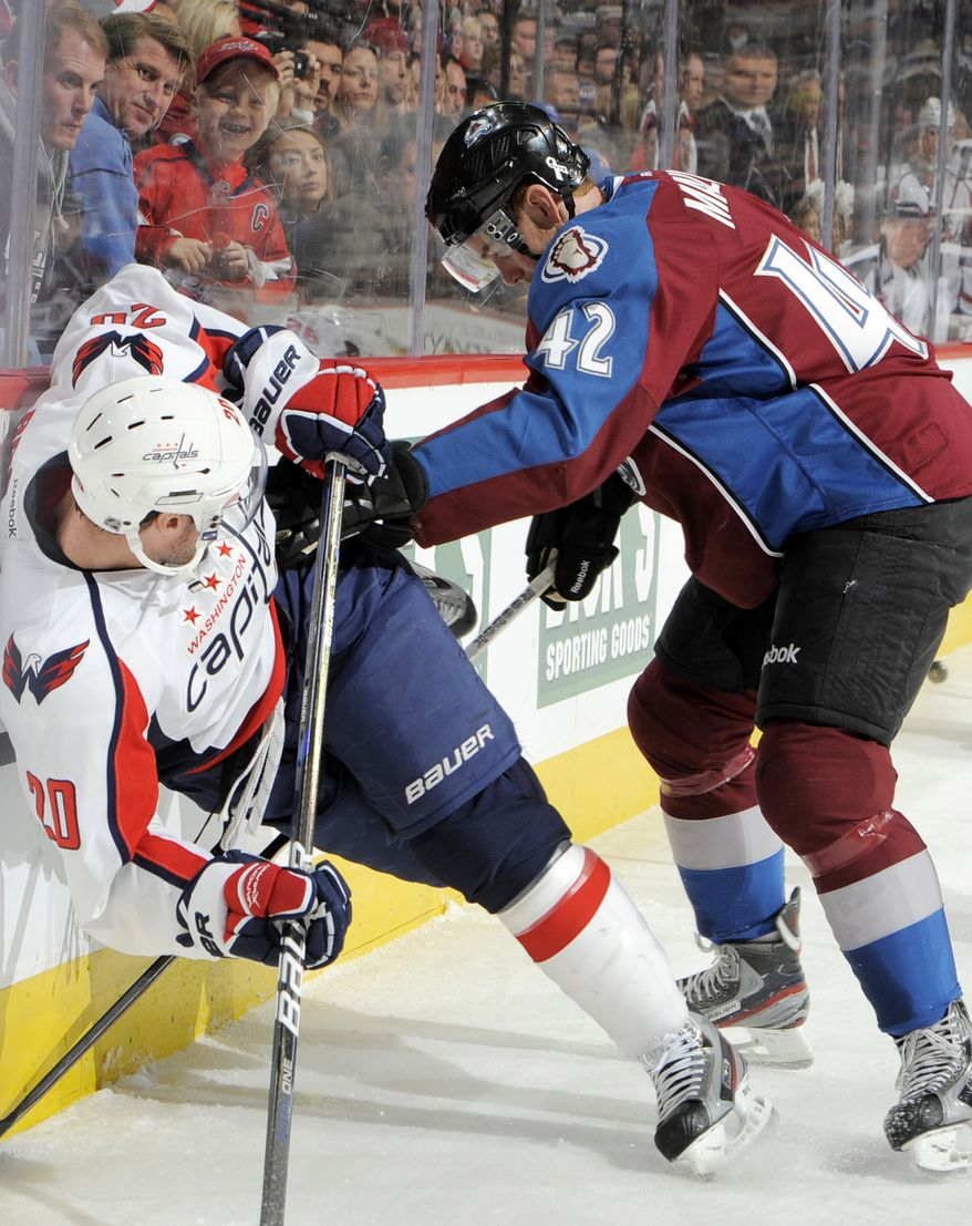 Colorado Avalanche center Brad Malone (42) knocks Washington Capitals left wing Troy Brouwer (20) off his skates during the first period Saturday, Dec. 17, 2011, in Denver. The Caps fell 2-1. (AP Photo/Jack Dempsey)