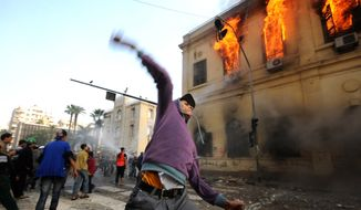 An Egyptian protester throws a stone toward soldiers, unseen, as a building burns during clashes near Tahrir Square, in Cairo, Egypt, Saturday, Dec. 17, 2011. (AP Photo/Ahmad Hammad)