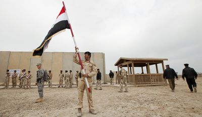 A member of the Iraqi army waves the national flag after a ceremony signing over Camp Adder, near Nasiriyah in Iraq, the last United States base in the country, to the Iraqi air force on Friday, Dec. 16, 2011. (AP Photo/Lucas Jackson, Pool)