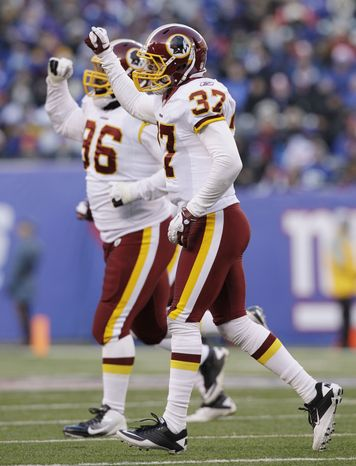 Washington Redskins' Reed Doughty (37), right, and teammate Barry Cofield react after New York Giants' Lawrence Tynes (not shown) missed a field goal during the third quarter Sunday, Dec. 18, 2011, in East Rutherford, N.J. The Redskins won 23-10. (AP Photo/Kathy Willens)