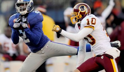 New York Giants' Kenny Phillips, left, intercepts a pass intended for Washington Redskins' Jabar Gaffney during the first quarter. (AP Photo/Bill Kostroun)