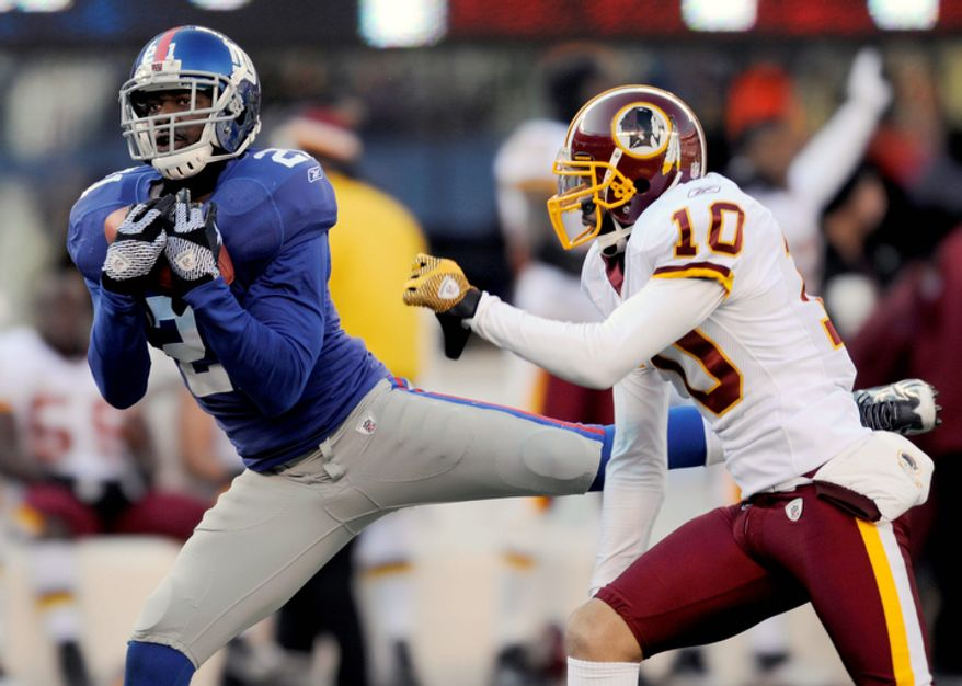 New York Giants' Kenny Phillips, left, intercepts a pass intended for Washington Redskins' Jabar Gaffney during the first quarter. (AP Photo/Bill Kostroun)