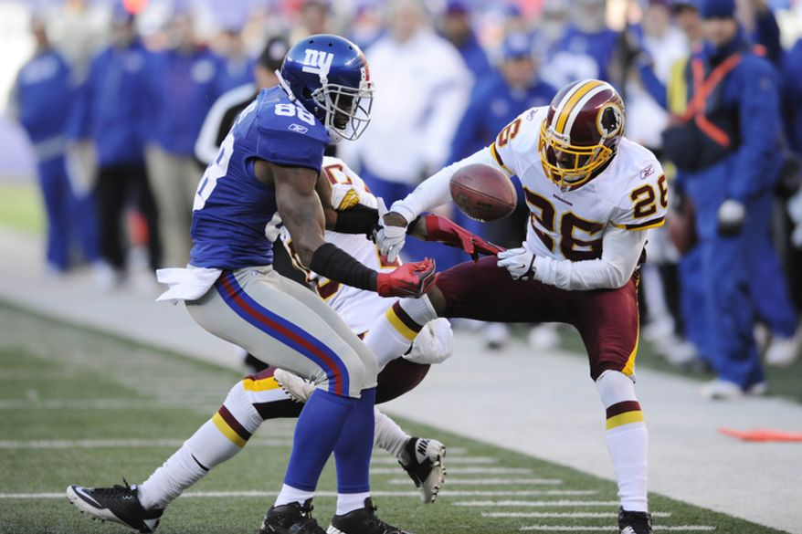 Washington Redskins' Josh Wilson, right, breaks up a pass intended for New York Giants' Hakeem Nicks during the second quarter. (AP Photo/Bill Kostroun)