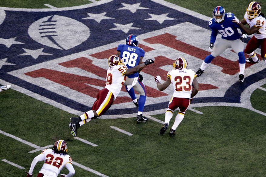 New York Giants wide receiver Hakeem Nicks (88) is tackled by Washington Redskins inside linebacker London Fletcher (59) during the third quarter. (AP Photo/Julio Cortez)