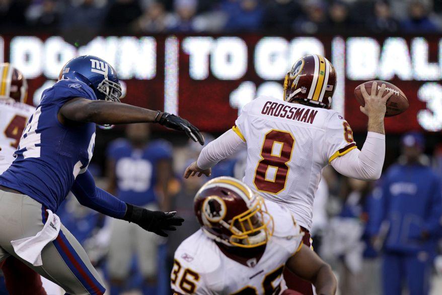 Washington Redskins quarterback Rex Grossman (8) looks to pass as New York Giants outside linebacker Mathias Kiwanuka (94) rushes during the third quarter. (AP Photo/Kathy Willens)