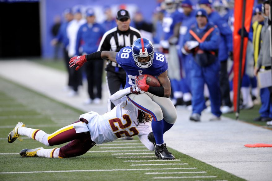 New York Giants wide receiver Hakeem Nicks (88) is tackled by Washington Redskins defensive back Kevin Barnes (22) during the third quarter. (AP Photo/Bill Kostroun)