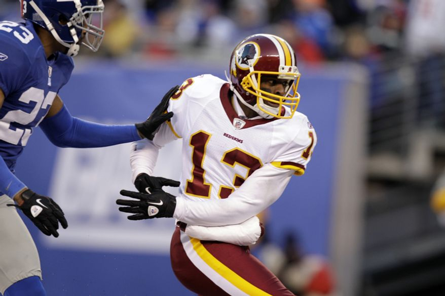 Washington Redskins wide receiver Anthony Armstrong (13) and New York Giants cornerback Corey Webster (23) play during the fourth quarter. (AP Photo/Kathy Willens)