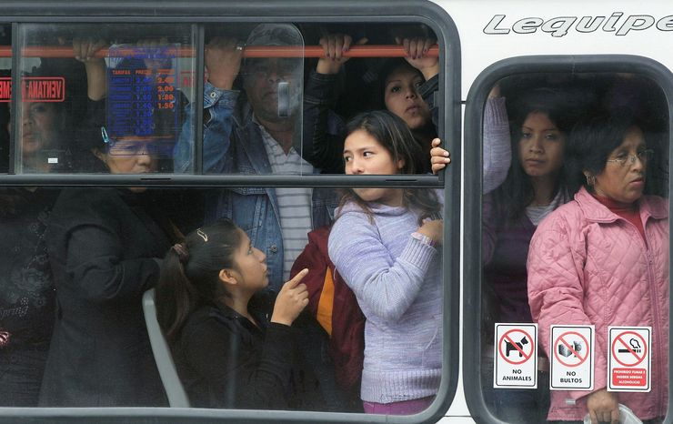Commuters ride a crowded bus in July. Lima has a new rapid transit bus system powered by natural gas, but an older fleet of buses spewing air pollution hasn't gone out of service yet. Air pollution in the capital exceeds World Health Organization limits ninefold. (Associated Press)