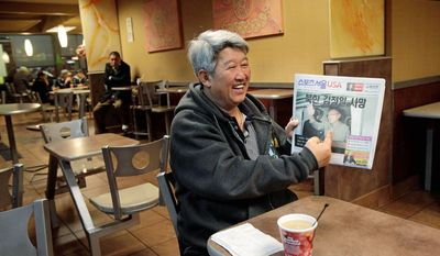 Korean immigrant Steve Park points to a photo of North Korean strongman Kim Jong-il in a newspaper over coffee at a McDonald's restaurant in Los Angeles on Monday. Mr. Kim died Saturday at age 69. (Associated Press)