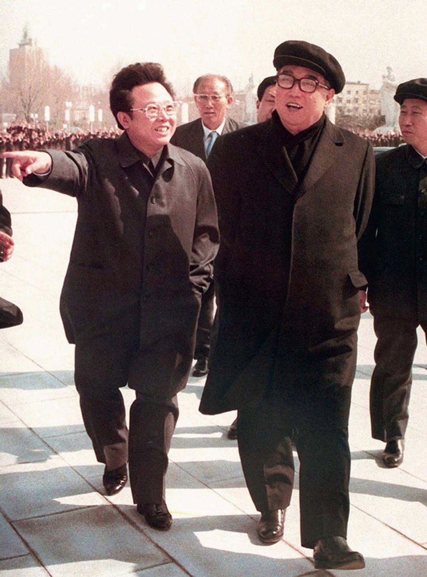 ** FILE ** In this April 1981 photo, Kim Jong-il (left) gestures while taking a stroll with his father, North Korean leader Kim Il-sung, in Pyongyang, North Korea. (AP Photo/Kyodo News)