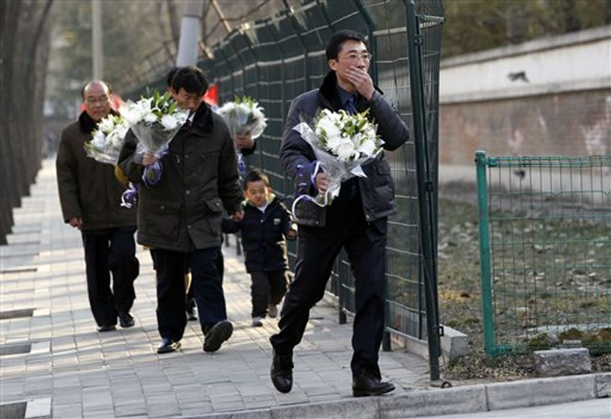 A man reacts as he walks with flowers towards the North Korean Embassy in Beijing on Monday, Dec. 19, 2011. Kim Jong-il, North Korea's mercurial and enigmatic leader, has died, North Korean state media announced Monday. (AP Photo/Ng Han Guan)