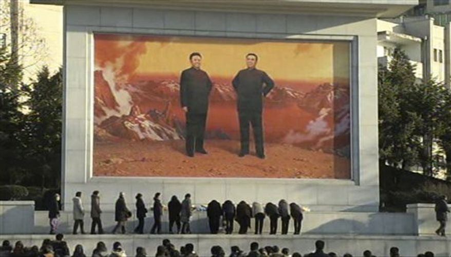 In this image made from Associated Press Television News, North Koreans mourn the death of North Korean leader Kim Jong-il in front of a mural depicting Mr. Kim and his father, Kim Il-sung, in Pyongyang, North Korea, on Monday, Dec. 19, 2011. (AP Photo/APTN)
