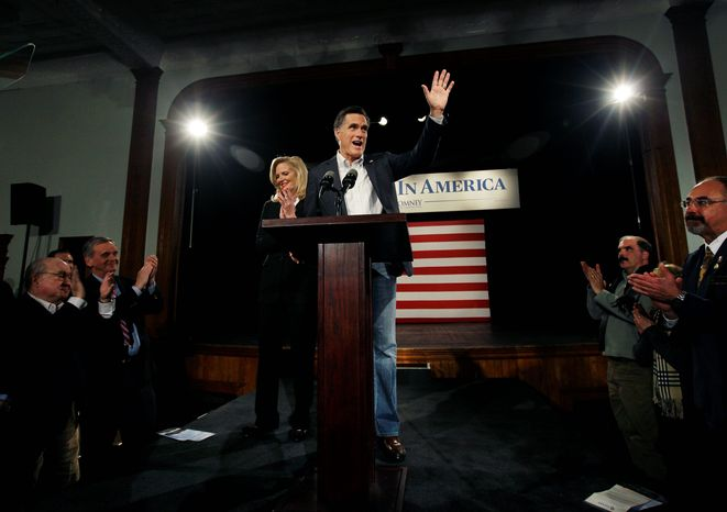 Republican presidential candidate Mitt Romney waves as he wife, Ann, applauds after a campaign speech in Bedford, N.H., on Tuesday. Mr. Romney indicated that he favors campaigns themselves being able to accept and spend donations of any size. (Associated Press)