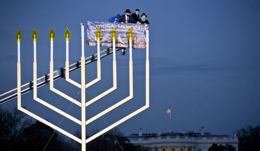 Rabbi Levi Shemtov, from left, Jacob J. Lew, Director of the Office of Management and Budget, and Rabbi Abraham Shemtov light the National Chanukah Menorah on the Ellipse in Washington, D.C. on Dec. 20, 2011. (T.J. Kirkpatrick/ The Washington Times) **FILE**