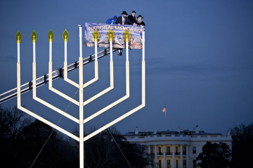 Rabbi Levi Shemtov, from left, Jacob J. Lew, Director of the Office of Management and Budget, and Rabbi Abraham Shemtov light the National Chanukah Menorah on the Ellipse in Washington, D.C. on Dec. 20, 2011.(T.J. Kirkpatrick/ The Washington Times)