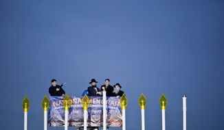 ** FILE ** Rabbi Abraham Shemtov (from right); Jacob Lew, director of the Office of Management and Budget; and Rabbi Levi Shemtov light the National Menorah on the Ellipse in Washington on Tuesday, Dec. 20, 2011, to mark Hanukkah. (The Washington Times)