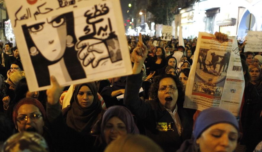 "Egyptian women angered by recent violence leveled against them in clashes between army soldiers and protesters demonstrate in Cairo on Tuesday, Dec. 20, 2011. One protester carries a poster that reads in English: ""Down with military rule, Military are liars and We will cut your hand."" (AP Photo/Nasser Nasser)"
