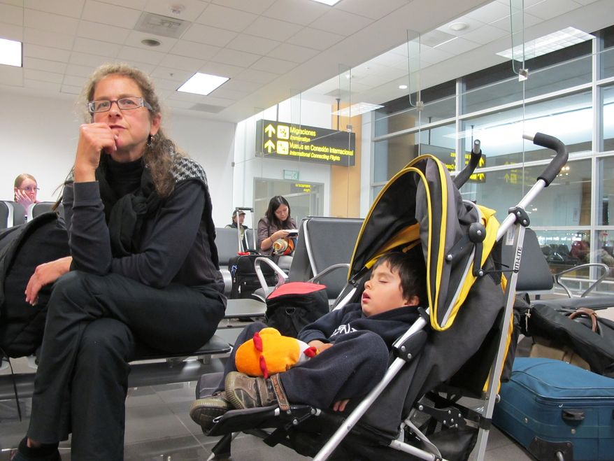 Paroled U.S. activist Lori Berenson, accompanied by her son, Salvador Apari, waits at the international airport in Lima, Peru, on Monday, Dec. 19, 2011, before boarding a plane to the United States. (AP Photo/Frank Bajak)