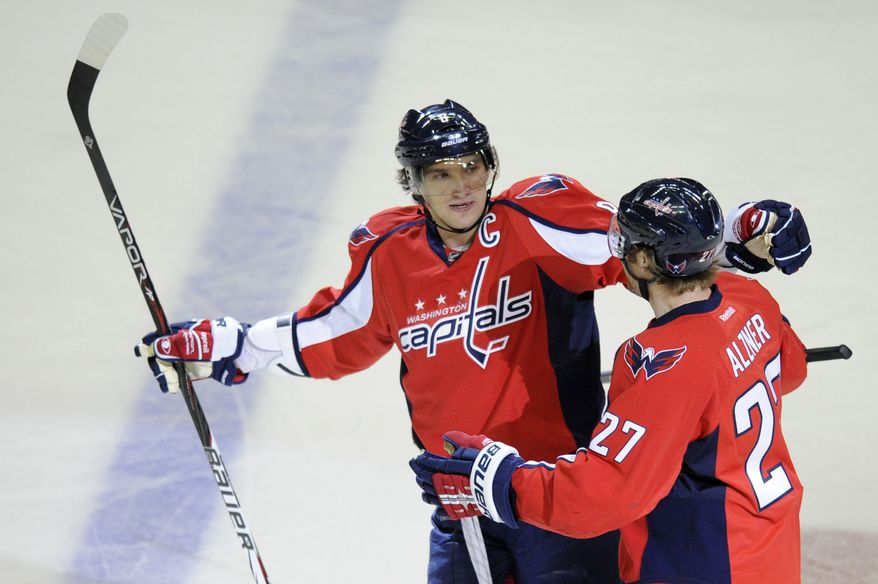 Washington Capitals left wing Alex Ovechkin (8) celebrates his goal with teammate Karl Alzner (27) during the first period of an NHL game against the Nashville Predators, Tuesday, Dec. 20, 2011, in Washington. (AP Photo/Nick Wass)