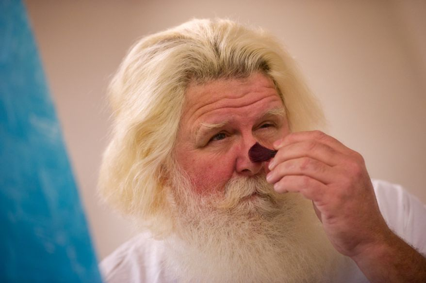 Michael Graham, who plays Santa, puts on makeup as he gets ready for his morning shift. This is Michael Graham's 22nd year as the Santa at Tyson's Corner Center. (Andrew Harnik / The Washington Times)