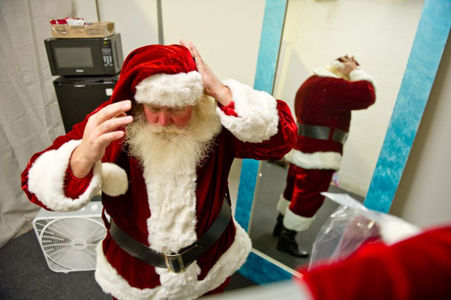 Michael Graham, who plays Santa, changes back into his Santa costume in his dressing room. (Andrew Harnik / The Washington Times)