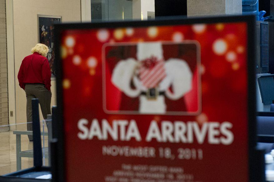 Michael Graham, who plays Santa, walks through Tyson's Corner Center before his morning shiftn. (Andrew Harnik / The Washington Times)
