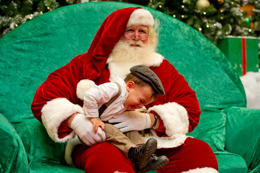 Michael Graham, who plays Santa at Tyson's Corner Center tries to calm a very upset 18 month year old, Thiago Heath of Falls Church, VA on his first visit with Santa. (Andrew Harnik / The Washington Times)